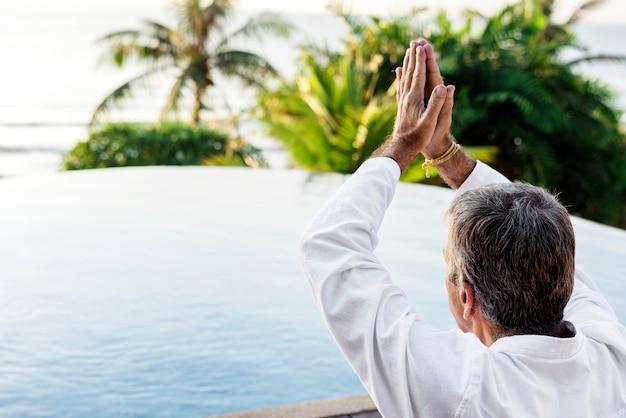 Idoso adulto praticando ioga à beira da piscina
