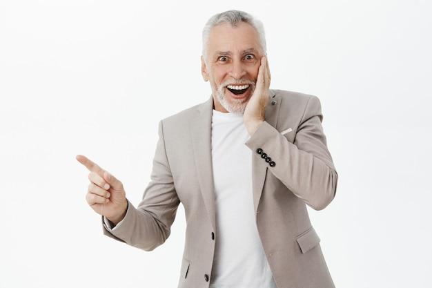 Idoso animado e surpreso apontando o dedo para a esquerda e sorrindo maravilhado