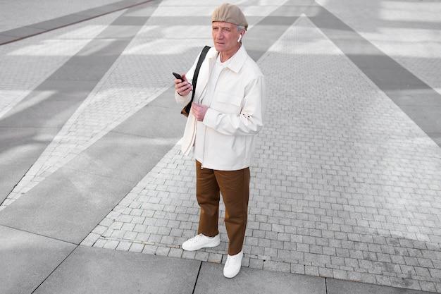 Idoso ao ar livre na cidade usando smartphone com fones de ouvido