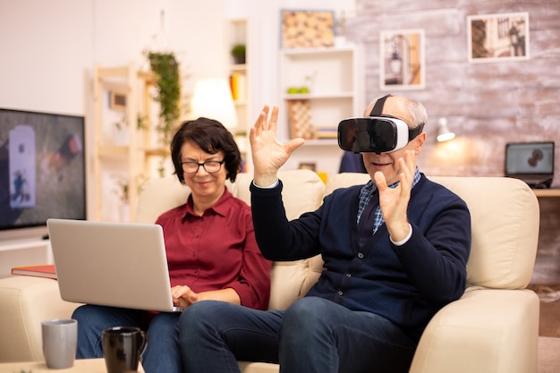 Idoso aposentado usando fone de ouvido de realidade virtual vr em seu apartamento aconchegante.