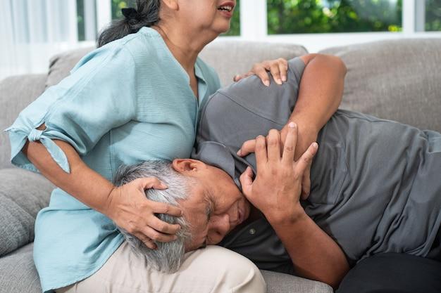 Idoso asiático está com dor e com as mãos no peito, tendo um ataque cardíaco