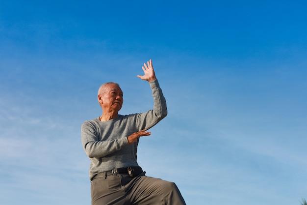 Idoso asiático praticando taichi chinês kungfu na praia