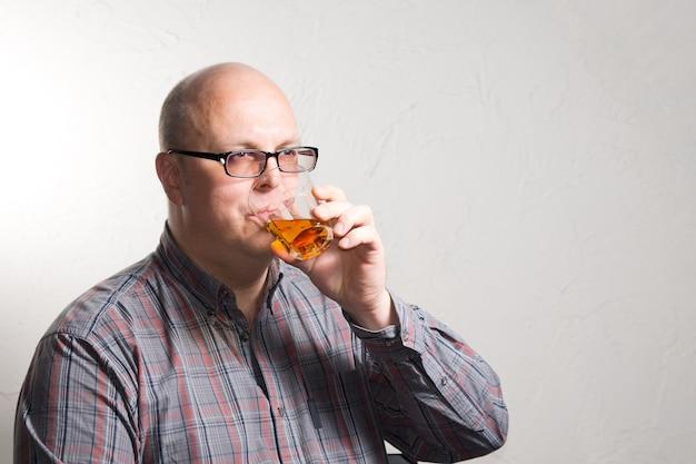 Idoso careca de óculos, bebendo um copo de conhaque ou uísque olhando para o lado com uma expressão séria