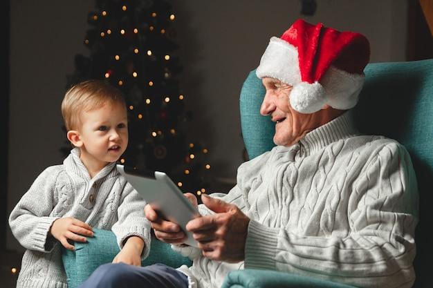 Idoso com chapéu de papai noel sentado em uma poltrona com o neto e usando um tablet