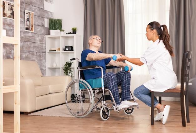 Idoso com dor nos braços, sentado em uma cadeira de rodas e treinando com halteres
