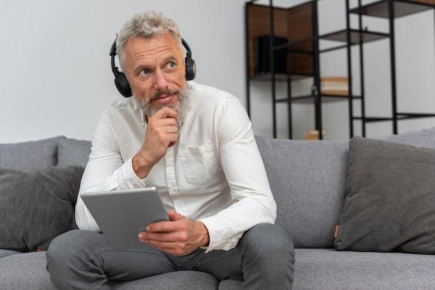 Idoso com fones de ouvido em casa usando um tablet