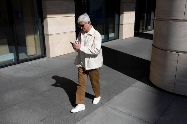 Idoso com óculos de sol ao ar livre na cidade usando smartphone enquanto toma café