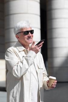 Idoso com óculos escuros ao ar livre na cidade falando ao telefone