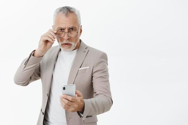 Idoso confuso de terno segurando um telefone celular e olhando