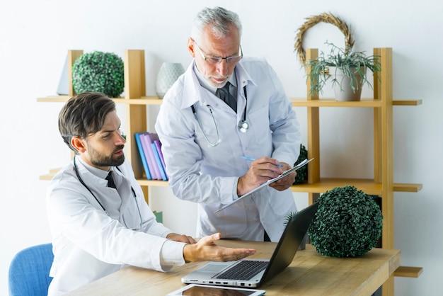 Idoso, doutor, fazer anotações, enquanto, ajudando, colega