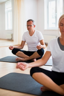 Idoso e mulher praticando ioga