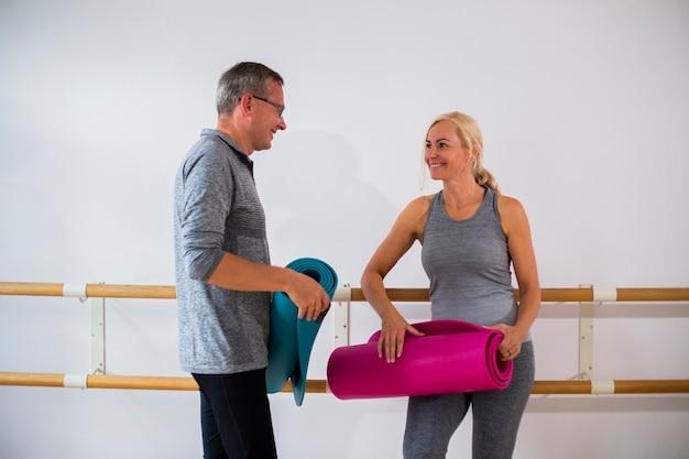 Idoso e mulher prontos para praticar ioga