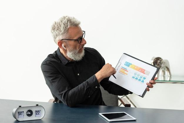 Idoso em casa mostrando gráfico no bloco de notas com o tablet na mesa