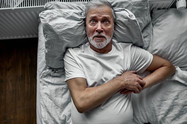 Idoso está sofrendo de ataque cardíaco na cama, segurando as mãos no peito, olhando para cima