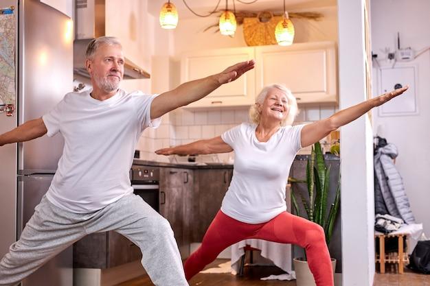 Idoso homem e mulher praticando virabhadrasana pose em casa, ioga. conceito de estilo de vida saudável