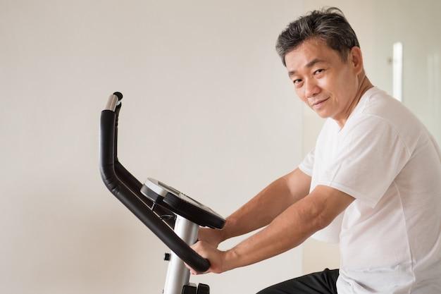 Idoso idoso andando de bicicleta, fazendo exercícios, malhando na academia com exercícios isocinéticos de máquina de ciclismo