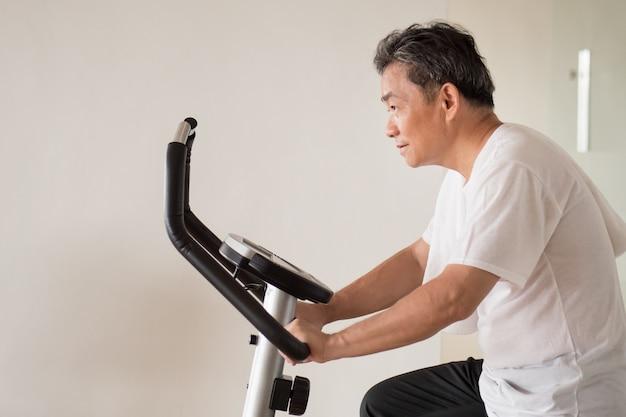 Idoso idoso andando de bicicleta, fazendo exercícios, malhando na academia com uma moderna máquina de ciclismo
