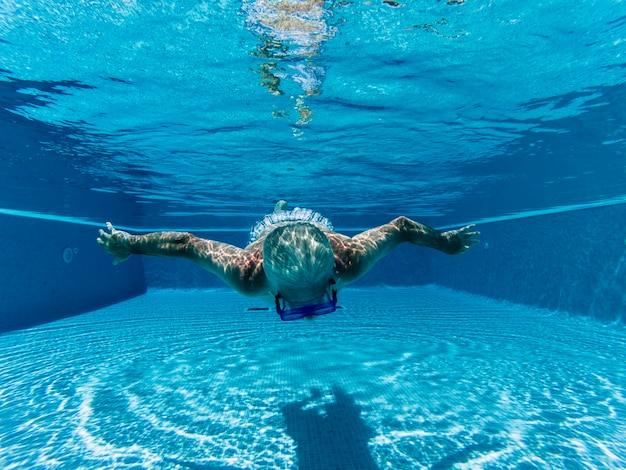 Idoso idoso nadando debaixo d'água em uma piscina azul com máscara de mergulho