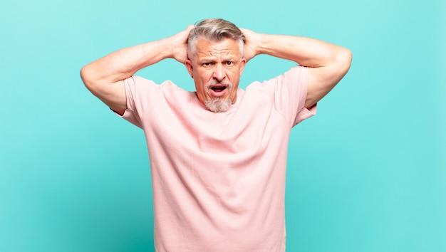 Idoso idoso sentindo-se estressado, preocupado, ansioso ou com medo, com as mãos na cabeça, entrando em pânico com o erro