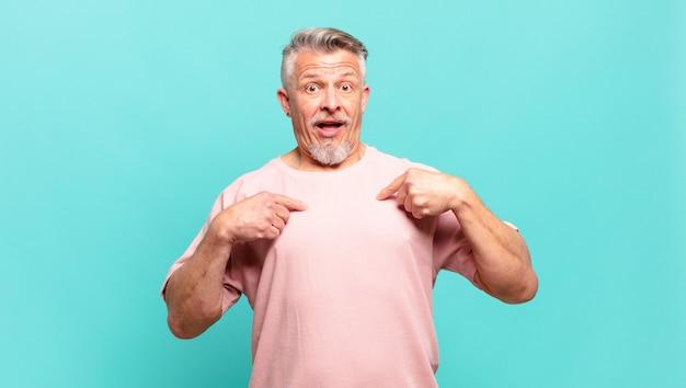 Idoso idoso sentindo-se feliz, surpreso e orgulhoso, apontando para si mesmo com um olhar animado e surpreso