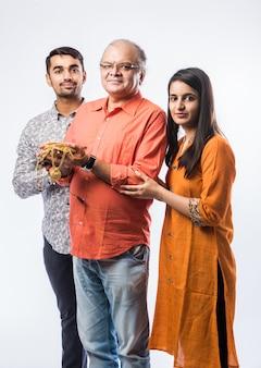 Idoso indiano com filho e filha ou casal segurando joias de ouro, enfeites