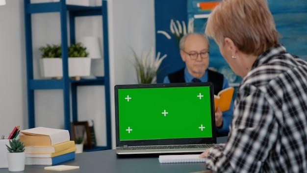 Idoso lendo na tela verde, mock up, display de chroma key do laptop, escrevendo no caderno trabalhando em casa. mulher sênior assistindo no pc com área de trabalho isolada, enquanto o homem está sentado no sofá