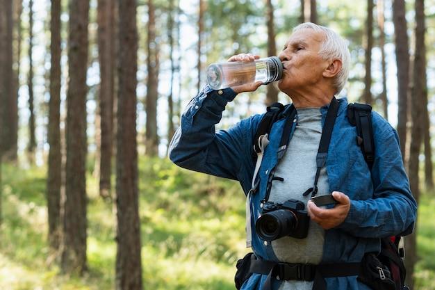 Idoso mantendo-se hidratado enquanto viaja ao ar livre