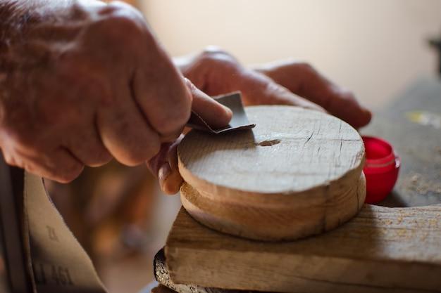 Idoso, mãos, esfregando, madeira, por, lixa