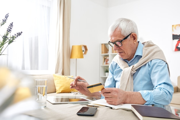 Idoso ocupado e enrugado de óculos usando tablet digital enquanto verifica o saldo do cartão de débito em casa