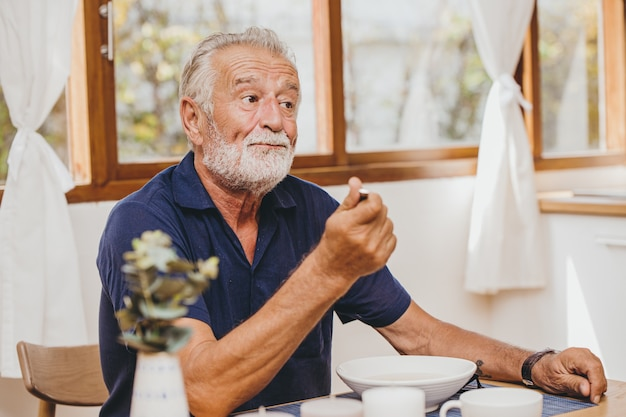 Idoso perda de apetite comida entediante gosto ruim infeliz ao comer a refeição durante a permanência em casa