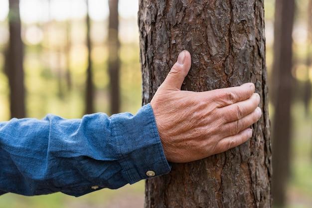 Idoso segurando uma árvore enquanto mochila