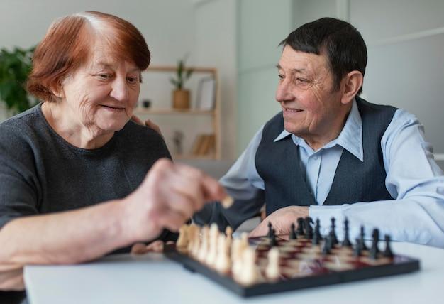 Idoso sorridente de tiro médio jogando xadrez