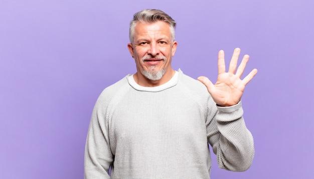Idoso sorrindo e parecendo amigável, mostrando o número cinco ou quinto com a mão para a frente, em contagem regressiva