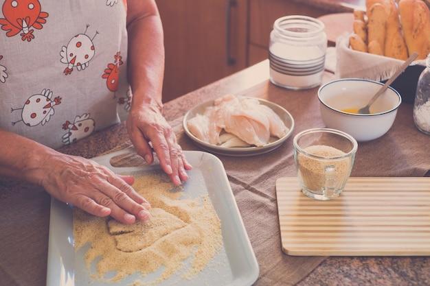 Idoso sozinho em casa cozinhando peixe na cozinha - muito focado em ambientes internos - mulher madura e caucasiana dos anos 60 - mulher aposentada