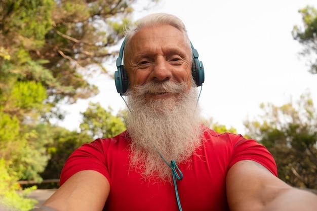 Idoso usando celular ao ar livre - homem maduro hipster se divertindo com as novas tendências, aplicativos para smartphone - pessoas, estilo de vida saudável, vida saudável e conceito de influenciador social