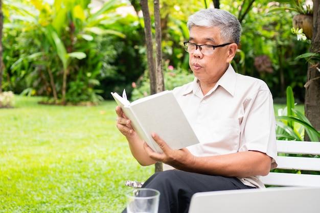Idoso velho lendo um livro no parque e bebendo água.