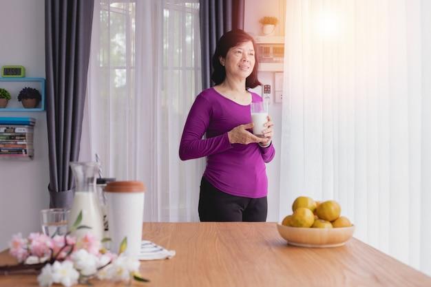 Idosos asiáticos beber um pouco de leite e olhando pela janela.