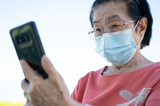 Idosos asiáticos felizes usando uma máscara facial e atendendo a uma videochamada usando seu smartphone no parque