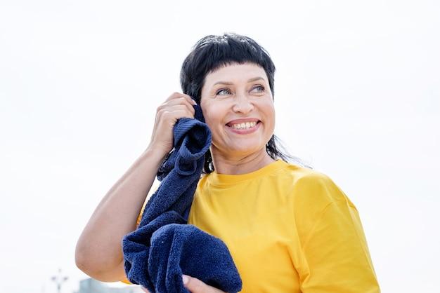Idosos ativos. mulher sênior enxugando o suor após um treino intenso ao ar livre no parque
