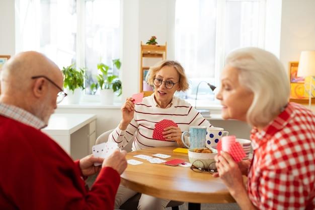 Idosos bonitos sentados em volta da mesa redonda jogando cartas