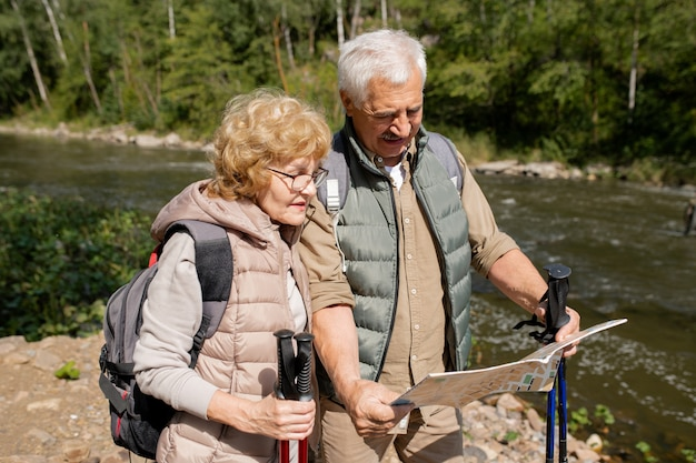 Idosos contemporâneos em roupas esportivas olhando o mapa do guia enquanto tentam encontrar o caminho de volta ou continuar sua viagem