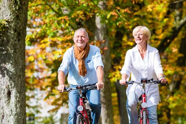 Idosos em bicicletas com passeio no parque