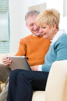 Idosos em casa com computador tablet