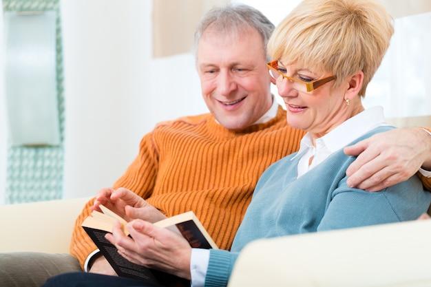Idosos em casa lendo um livro juntos