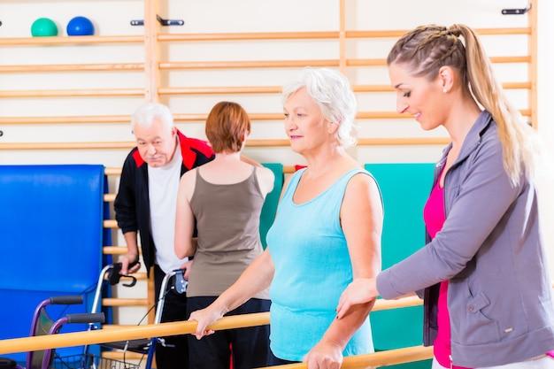 Idosos em terapia de reabilitação física com treinador