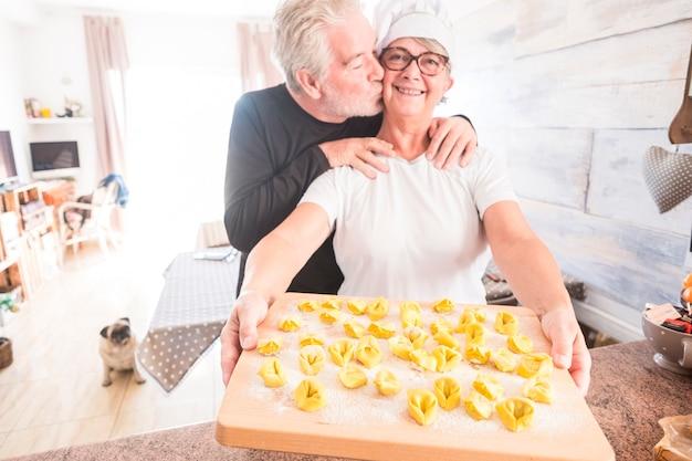 Idosos felizes desfrutando da atividade doméstica em casa, cozinhando tortellini italiano saudável, macarrão com comida