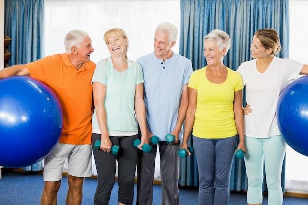Idosos segurando bola e pesos de exercício