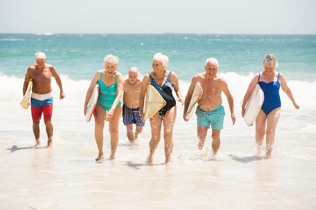 Idosos segurando pranchas de surf na praia
