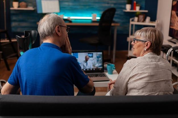 Idosos usando videochamada em laptop com dentista