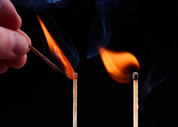 Ignição de um fósforo, com fumaça em fundo escuro. mão segurando um palito de fósforo aceso